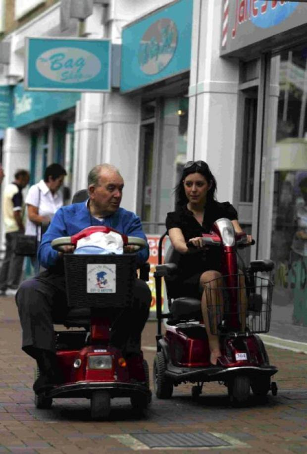HELPFUL: Percy Toms raised lot of money and awareness for Shopmobility – here he is showing Echo reporter Emma Joseph how to use a scooter three years ago