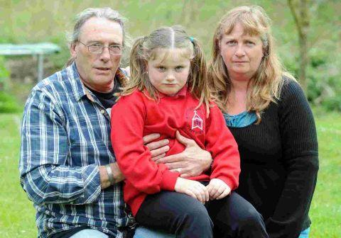 TEARS: Kris and Helen Dutson with daughter Katie who was left alone on the A35 after being dropped off the school bus