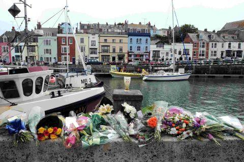 SADLY MISSED: Floral tributes to the three fishermen are laid at the vacant berth of the Purbeck Isle on Weymouth harbourside