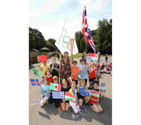 Olympic torch bearer Ann Nugent joins children at Verwood First School at an opening ceremony at the beginning of their Olympics week