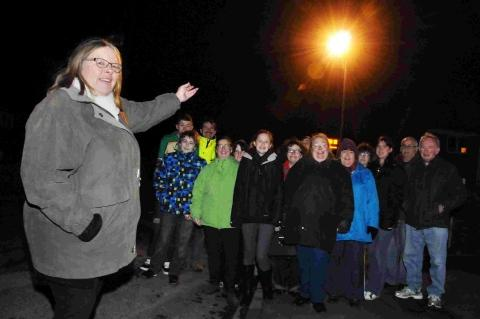 SWITCHED ON: Gill Paterson and other Littlemoor residents under a street light outside the entrance to Littlemoor Community Centre in Canberra Road