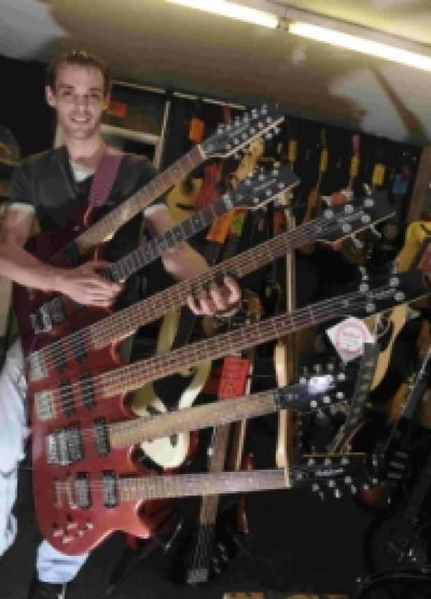 RARE WAY TO BACKACHE: Shane Churchill getting to grips with the six-neck guitar