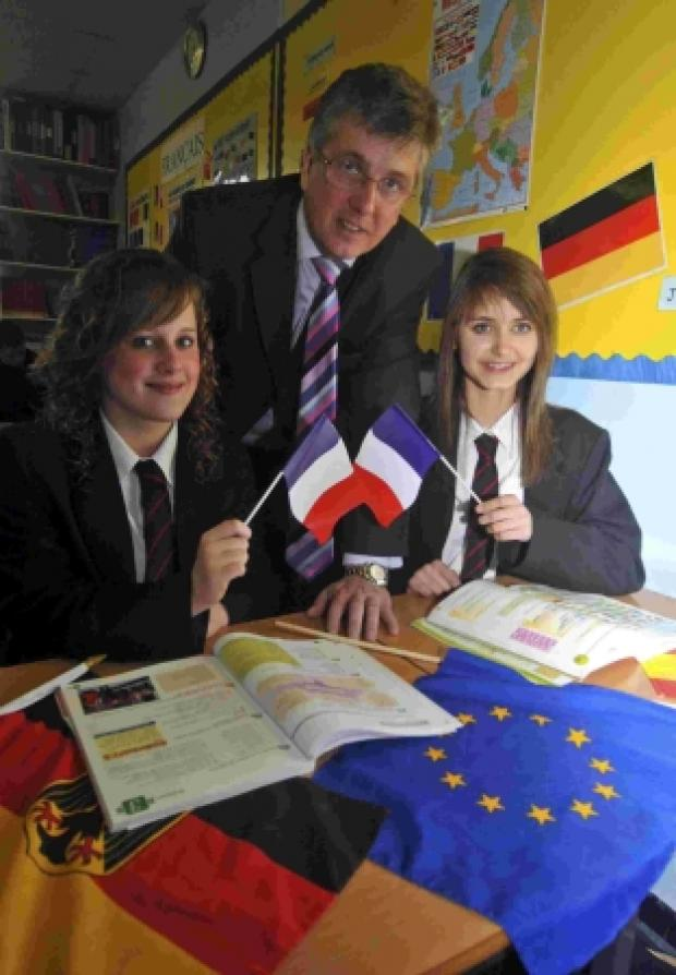 NOW WE'RE TALKING: All Saints head Tim Balmforth with pupils Farrin Aitken, left and Katie House celebrate the school's specialist language status